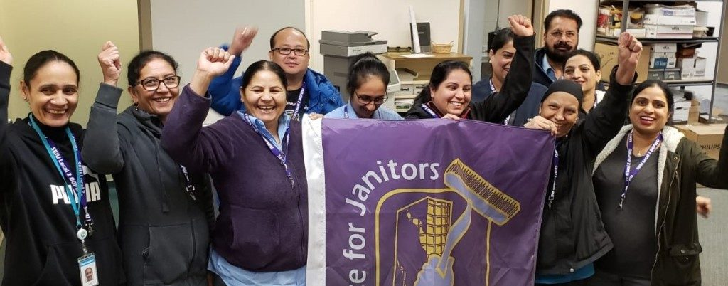 Janitors from the BC Hydro site in Surrey gathered around an SEIU flag