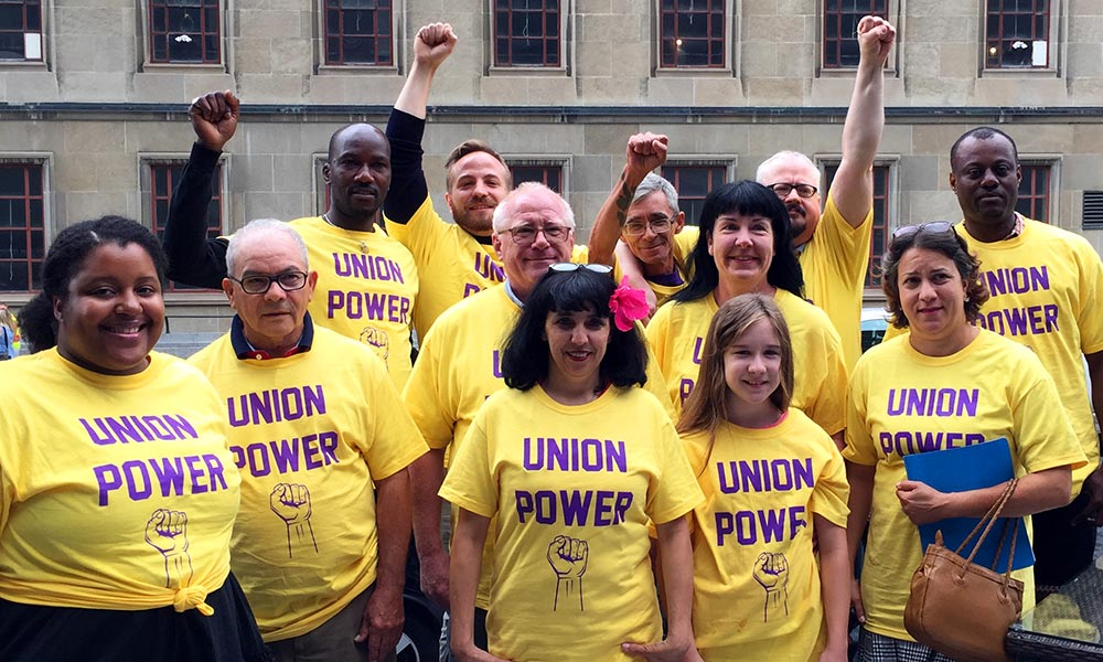 Workers stand in Union Power shirts
